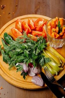 Świeże pokrojone warzywa na drewnianej desce. przekąska świeżych pomidorów, ogórków, rzodkiewki i zioła widok z góry pojęcie zdrowego odżywiania, dieta, wegetarianizm.
