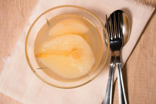 Świeże pół gruszki podawane ze słodkim syropem. tło drewniany stół.