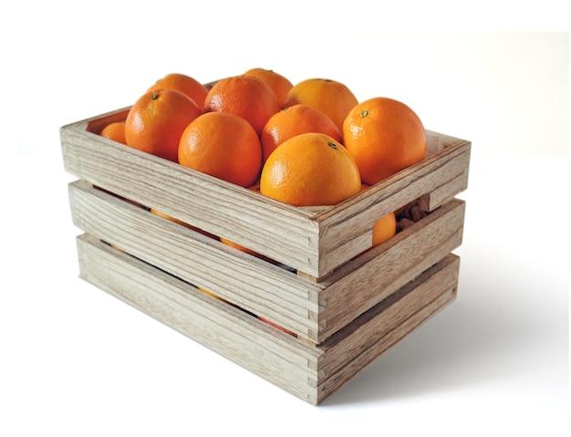 Świeże pomarańcze w drewnianym pudełku, odizolowane od białego tła