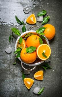 Świeże pomarańcze w rondlu z kostkami lodu i liśćmi na kamiennym stole. widok z góry
