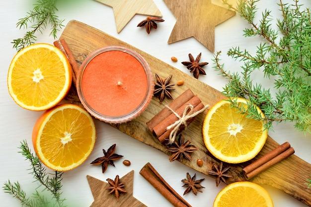 Świeże pomarańcze z anyżem, laskami cynamonu, gałązkami jałowca i świecą zapachową