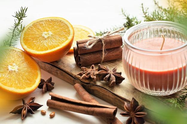 Świeże pomarańcze z anyżem, laski cynamonu, gałązki jałowca i świeca zapachowa, kompozycja świąteczna
