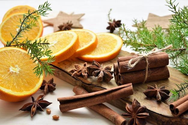 Świeże pomarańcze z anyżem, laski cynamonu, gałązki jałowca. wesołych świąt bożego narodzenia skład czasu