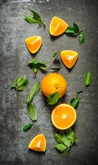 Świeże pomarańcze z liśćmi. na kamiennym stole. widok z góry