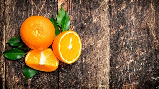 Świeże pomarańcze z zielonymi liśćmi na drewnianym tle
