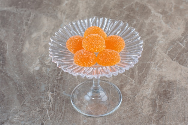 Świeże pomarańczowe cukierki na szklanych naczyniach na szarej powierzchni.