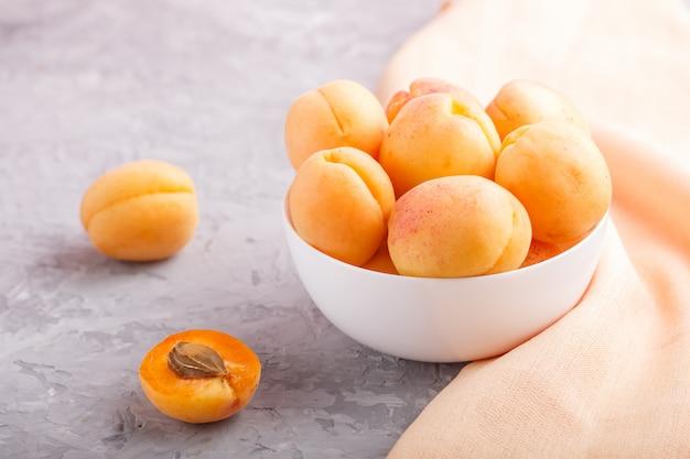 Świeże pomarańczowe morele w białym pucharze. widok z boku.