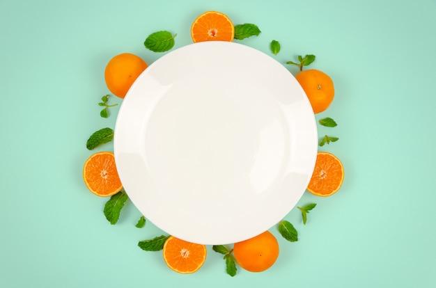 Świeże pomarańczowe owoc i nowi liście z bielu talerzem i zielonego koloru tłem.