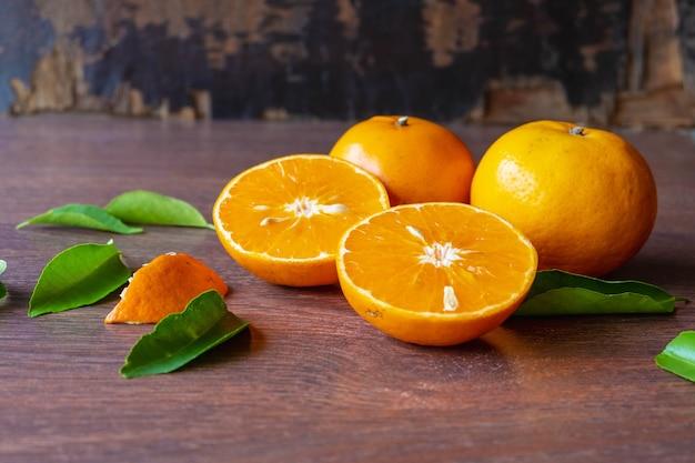 Świeże pomarańczowe owoce i pomarańczowe owoce przecięte na pół na drewnianym stole