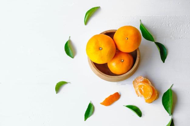 Świeże pomarańczowe owoce na drewnianej misce