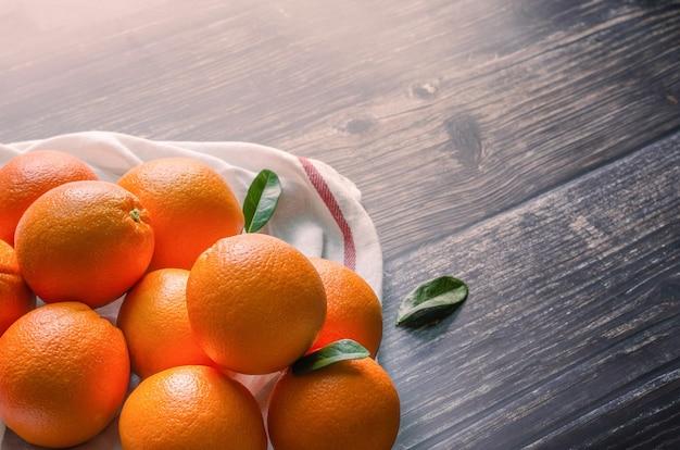 Świeże pomarańczowe owoce z liśćmi na drewnianym stole i światło słoneczne rano.