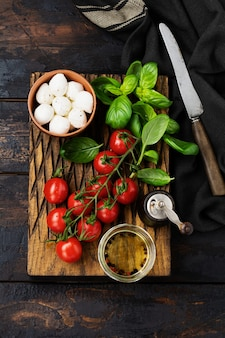 Świeże pomidorki koktajlowe, liście bazylii, ser mozzarella i oliwa z oliwek na starej powierzchni drewnianych. składniki sałatki caprese. selektywne skupienie.