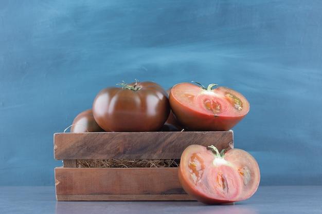 Świeże pomidory całe i pokrojone w drewniane pudełko.