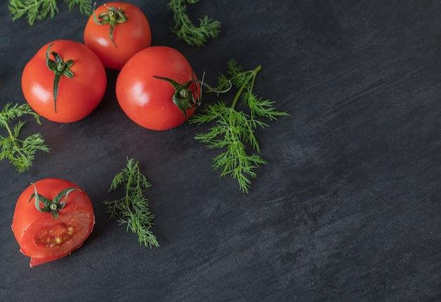 Świeże pomidory całe z zieleniną na ciemnym tle.