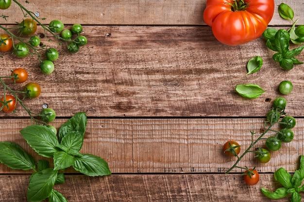 Świeże pomidory cherry gałęzie, liście bazylii, młynek do serwetek, pieprzu i pieprzu na starym drewnianym tle rustykalnym. jedzenie gotowanie tło i makiety.
