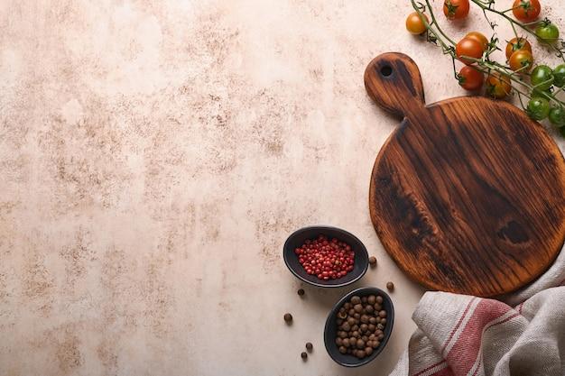 Świeże pomidory cherry gałęzie, serwetka, pieprz czerwony i czarny na tle białego marmuru stoiska. jedzenie gotowanie tło i makiety.