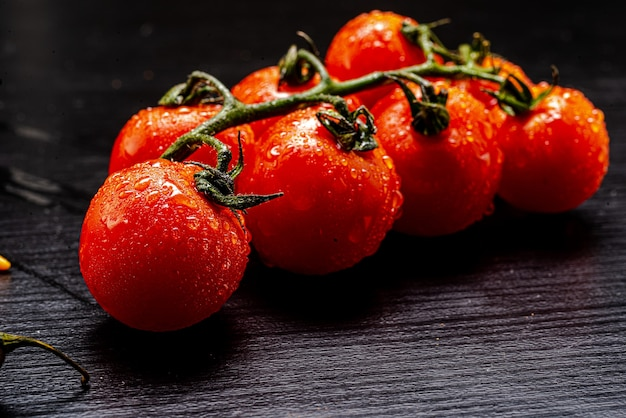 Świeże pomidory czereśniowe na czarnym stole z przyprawami. widok z góry z miejscem na kopię.