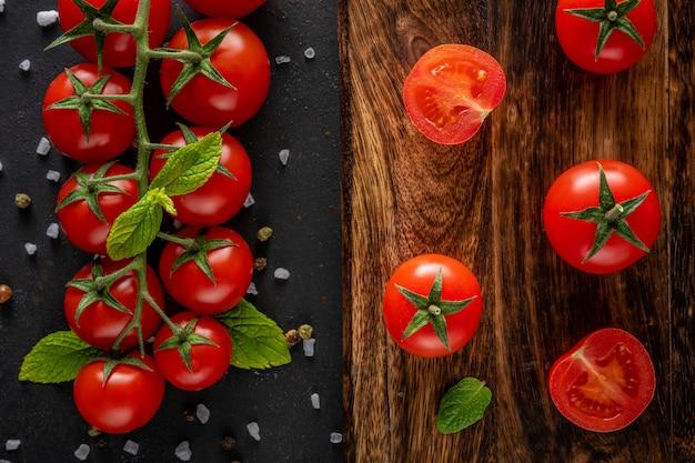 Świeże pomidory czereśniowe na czarnym tle z przyprawami.