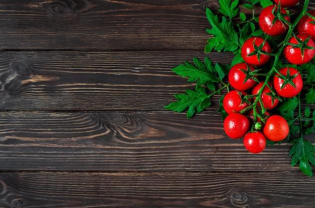 Świeże pomidory czereśniowe na gałęzi z liśćmi