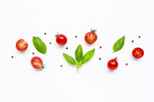 Świeże pomidory czereśniowe z liśćmi bazylii i różnego rodzaju pieprzu na białym widok z góry