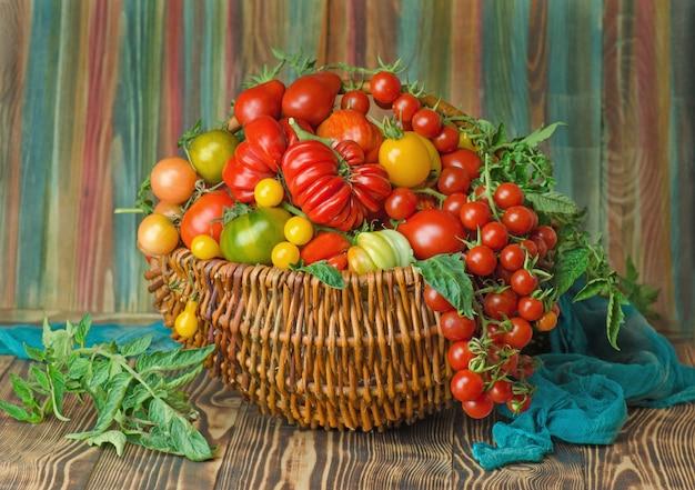 Świeże pomidory czerwone w koszu w kuchni. pomidory w wiklinowym koszu w kuchni
