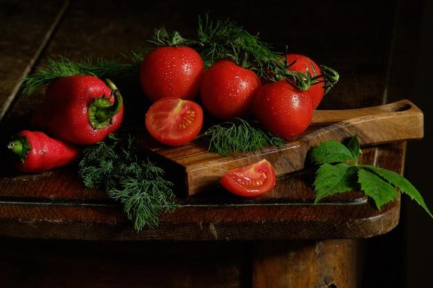 Świeże pomidory i koper na ciemnym drewnianym stole na czarnym tle