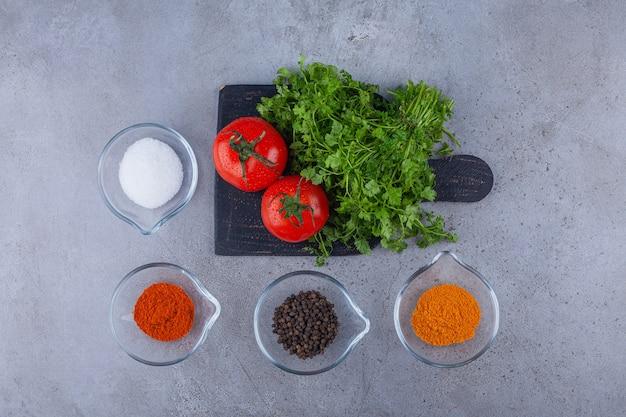 Świeże pomidory i liście pietruszki na czarnej desce do krojenia z przyprawami.