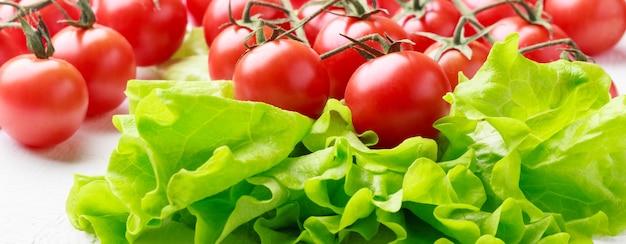 Świeże pomidory i sałata na białym drewnianym tle