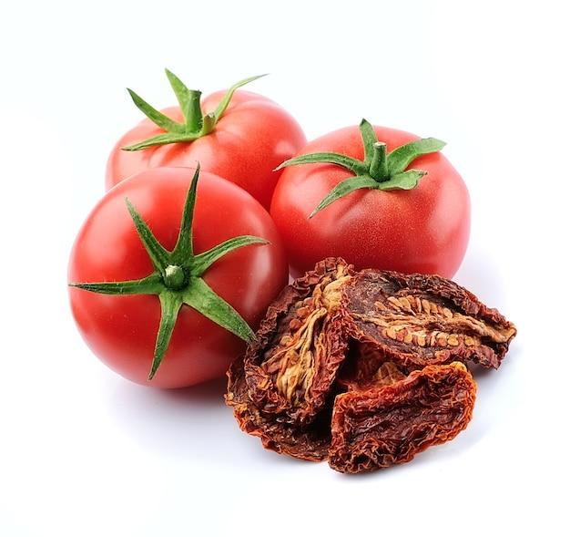 Świeże pomidory i suszony pomidor na białym tle.