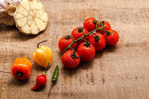 Świeże pomidory koktajlowe na rustykalnym brązowym drewnianym stole z kilkoma paprykami i pokrojonym w plasterki czosnkiem. widok z góry