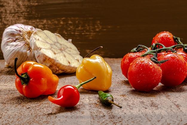 Świeże pomidory koktajlowe na rustykalnym brązowym drewnianym stole z kilkoma paprykami i pokrojonym w plasterki czosnkiem.