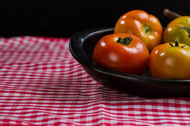 Świeże pomidory na czarnej płycie na kraciastej tkaninie