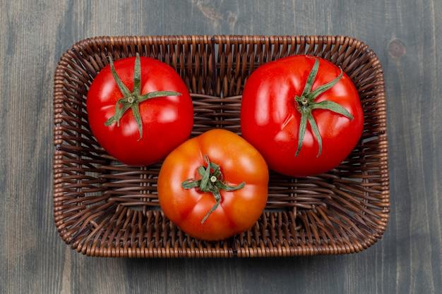 Świeże pomidory soczyste w wiklinowym koszu