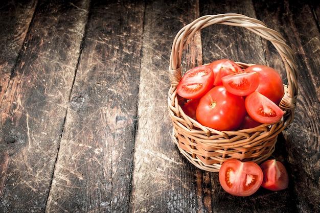 Świeże pomidory w koszu. na drewnianym tle.