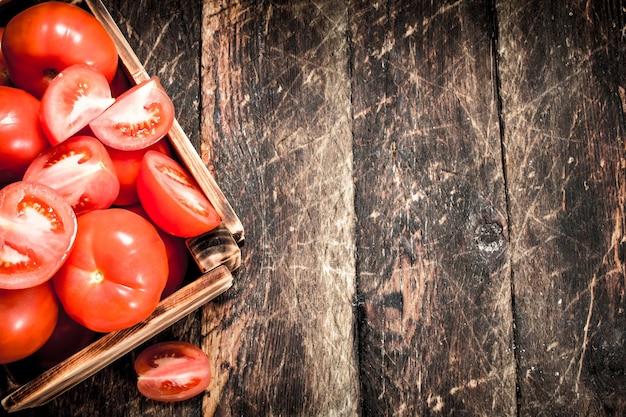 Świeże pomidory w starym pudełku. na drewnianym tle.