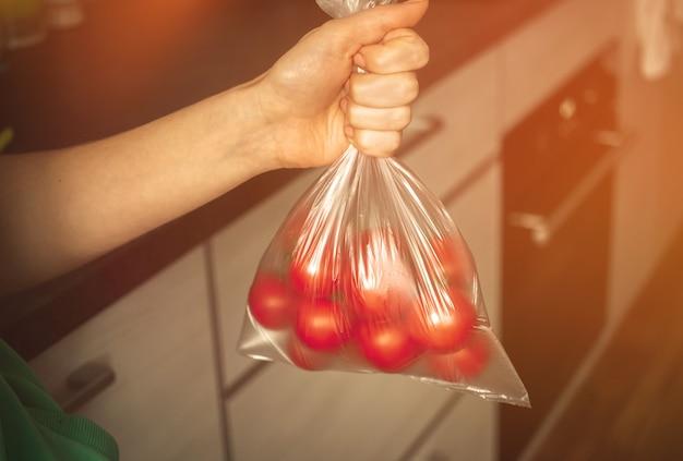 Świeże pomidory w torbie na tle kuchni