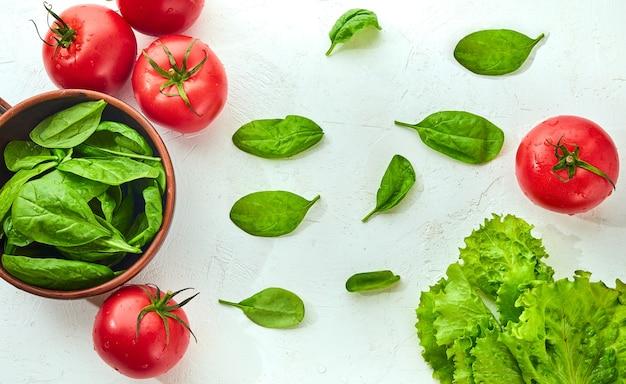 Świeże pomidory winogronowe z sałatką i szpinakiem liście na białym tle. koncepcja gotowania.