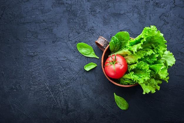 Świeże pomidory winogronowe z sałatką i szpinakiem liście na czarnym tle kamienia.