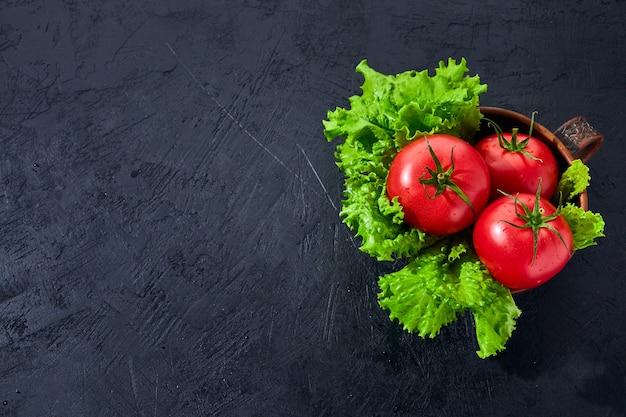Świeże pomidory winogronowe z sałatką liście na czarnym tle kamienia koncepcja gotowania ziołowych pomidorów