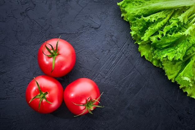 Świeże pomidory winogronowe z sałatką liście na czarnym tle kamienia. zioła, pomidory, koncepcja gotowania.