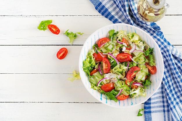 Świeże pomidory z ogórkiem, sałatą, czerwoną cebulą i przyprawami w białej misce. koncepcja zdrowej przekąski. białe tło drewniane. widok z góry, narzut, miejsce na kopię