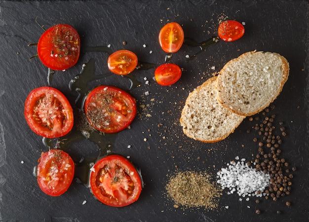 Świeże pomidory z oliwą z oliwek i solą. na czarnej rustykalnej powierzchni