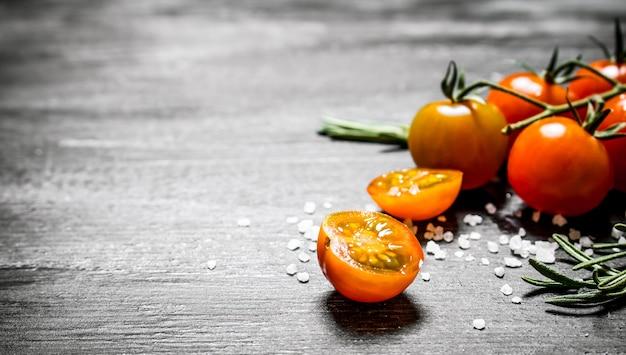 Świeże pomidory z solą i rozmarynem. na czarnym tle rustykalnym.