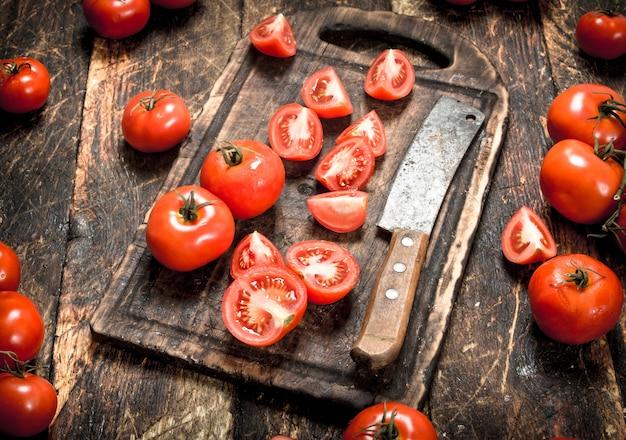 Świeże pomidory z stary topór na desce do krojenia na drewnianym tle