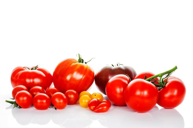 Świeże pomidory z zielonymi liśćmi na białym tle