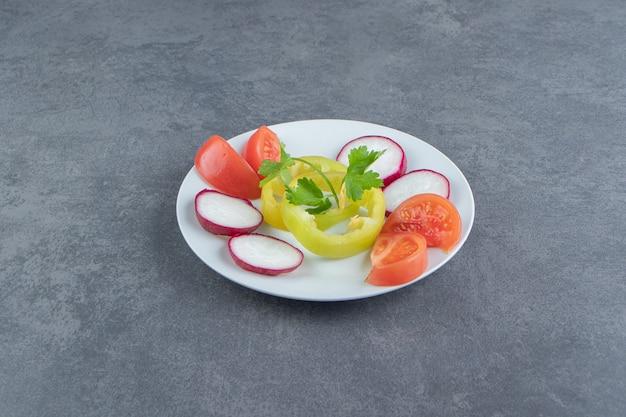 Świeże posiekane warzywa na białym talerzu.