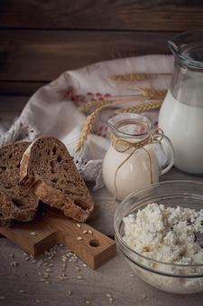 Świeże produkty mleczne. mleko, twarożek, śmietana, domowy chleb wieloziarnisty i pszenica na rustykalne drewniane tła. koncepcja mleczarstwa ekologicznego.