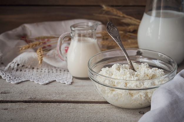 Świeże produkty mleczne: mleko, twarożek, śmietana i pszenica na rustykalne drewniane tła. koncepcja mleczarstwa ekologicznego.
