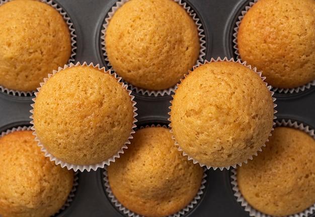 Świeże pyszne babeczki w naczyniu do pieczenia babeczki waniliowe widok z góry tekstura babeczki