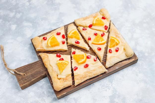 Świeże pyszne ciasto francuskie z pestkami granatu i plasterkami pomarańczy na betonie
